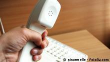 Symbolbild Hand am Telefonhörer