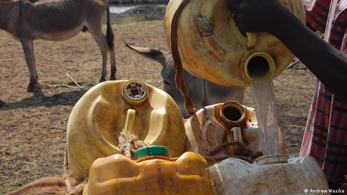 Water being poured into a can in Turkana, Kenya