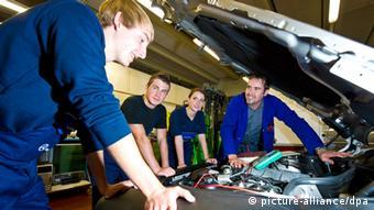 Azubis in Sindelfingen begutachten einen Motor. Foto: Daniel Bockwoldt/dpa