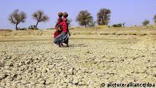 Das Archivbild vom April 2000 zeigt Bewohnerinnen des Dorfes Bambariyon-ki-Dhani im indischen Bundesstaat Rajasthan, die über das verdörrte Land laufen, um sich Trinkwasser zu beschaffen. Mehr als 250 Millionen Menschen in über 110 Ländern - vor allem in Afrika - sind nach Angaben des UN-Wüstensekretariats unmittelbar von Wüstenbildung bedroht. Rund 1,2 Milliarden Menschen seien mittelbar durch Verödung von Böden gefährdet. Jährlich gingen durch Wüstenbildung rund zehn Millionen Hektar Land verloren - das ist etwa die Fläche der Bundesländer Bayern und Baden-Württemberg. Zu wenig fruchtbares Ackerland und Wassermangel führe zu Armut und Entwurzelung. Am Montag (11.12.2000) begann in Bonn eine zweiwöchige UN-Wüstenkonferenz. dpa
