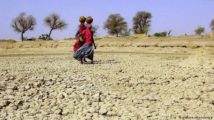 Two women walking over dry and cracked land, carrying water pots on their heads
