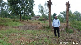 François Kabagema is standing in front of the two trees he planted as a boy. Photo: Copyright: Anne Le Touzé, DW