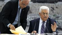 Palestinian president Mahmud Abbas (R) gestures as he signs a request to join 15 United Nations agencies at his headquarters in the West Bank city of Ramallah on April 1, 2014, in a move that could derail a US push to revive faltering peace talks with Israel. AFP PHOTO / ABBAS MOMANI (Photo credit should read ABBAS MOMANI/AFP/Getty Images)