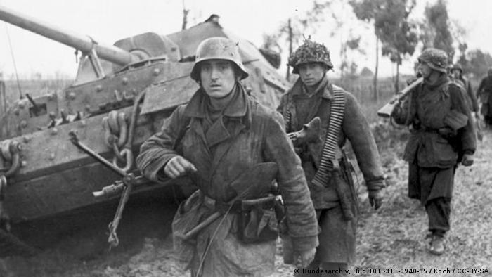Três soldados caminhando em frente a tanque