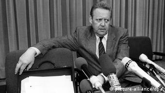 Foto em preto e branco com homem diante de vários microfones