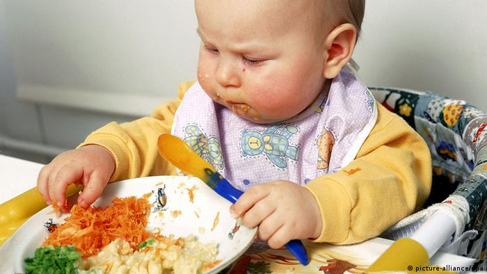 A baby sits at a high-chair eating from a plate of food