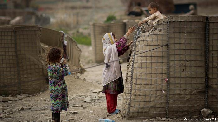 An Afghan girl helps her brother down from a security barrier set up outside the Independent Election Commission (IEC) office in the eastern Afghan city of Khost, Thursday, April 3, 2014.