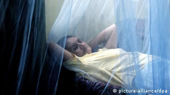 A Honduran woman behind a mosquito bed net suffering from dengue hemorrhagic fever (Photo: EPA/GUSTAVO AMADOR)
