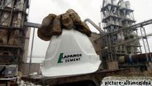 ARCHIV - Ein Schutzhelm mit dem Logo der «Lafarge Zement GmbH» liegt am 10.03.2004 vor der Kulisse der Schachtvorwärmer in Karsdorf (Burgenlandkreis). Foto: Peter Endig/dpa (zu dpa «Holcim und Lafarge wollen zu weltgrößtem Zementkonzern fusionieren» vom 07.04.2014) +++(c) dpa - Bildfunk+++
