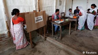A woman (L) casts her vote with an electronic voting machine as others get their voting slip from an officer at a polling station in Majuli, a large river island in the Brahmaputra river, Jorhat district, in the northeastern Indian state of Assam April 7, 2014.