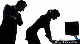 Девушка стоит у компьютера, а мужчина сзади рассматривает ее фигуру