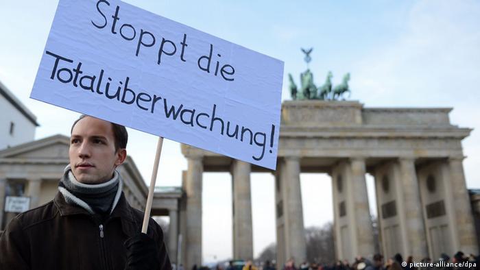 Stoppt die Totalüberwachung, fordert ein Mann, der vor dem Brandenburger Tor in Berlin gegen die Vorratsdatenspeicherung demonstriert (Foto: dpa)