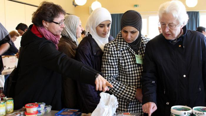 Andrea von Schmude helping Syrian women refugees at the food bank in Bornheim (Photo: Juli Rutsch, DW)