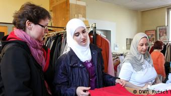 Von Schmude (left) helps Raghed (middle) at the clothing bank (Photo: Juli Rutsch, DW)