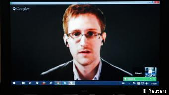 Edward Snowden is seen on a screen as he speaks via video conference