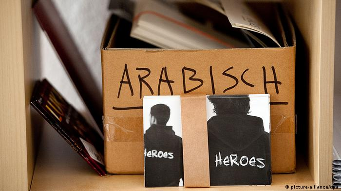 two postcards that read heroes propped up on box that says Arabic.