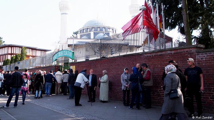 Gläubige vor der Grundstücksmauer der Sehitlik-Moschee