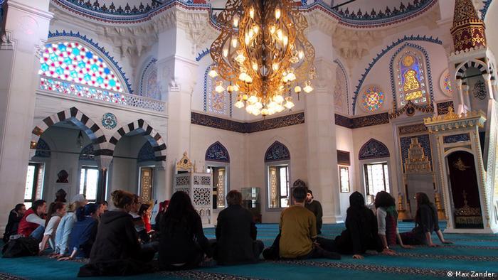 Eine Besuchergruppe hört im Gebetsraum einen Vortrag