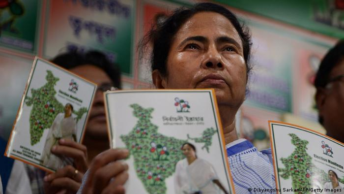 Mamata Banerjee holds up a copy of her party's manifesto