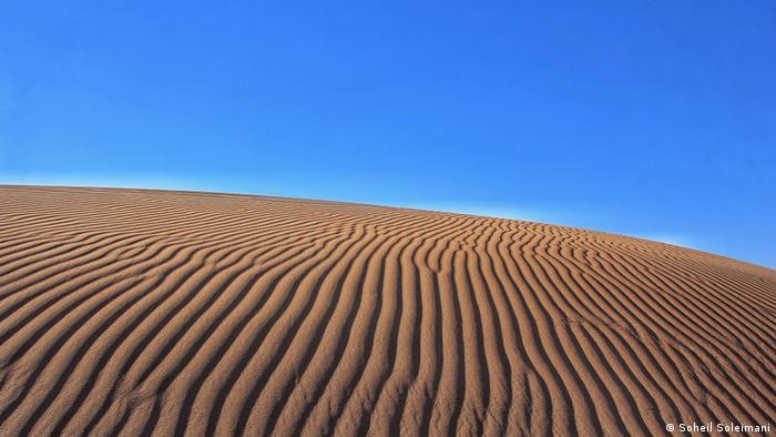 Sand dune under a blue sky (Photo: Soheil Soleimani)