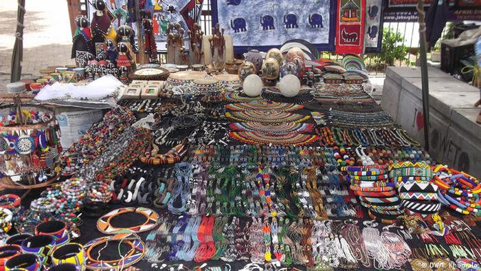 A market stall full of brightly colored artworks and trinkets