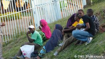 People on the grass outside Kasarani Stadium wait for news of their relatives