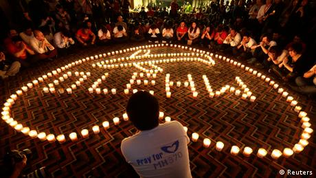 Candles spell out MH 370 in a heart shaped border