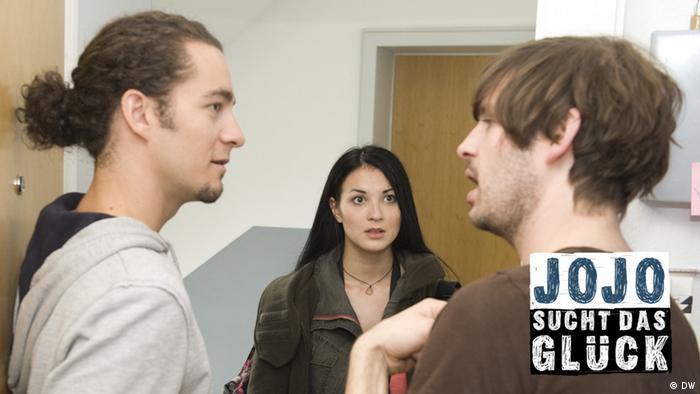 Jojo im Gespräch mit Marc und Reza vor ihrer Wohnungstür.