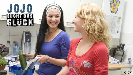 Zwei junge Frauen bereiten in der Küche Salat zu.