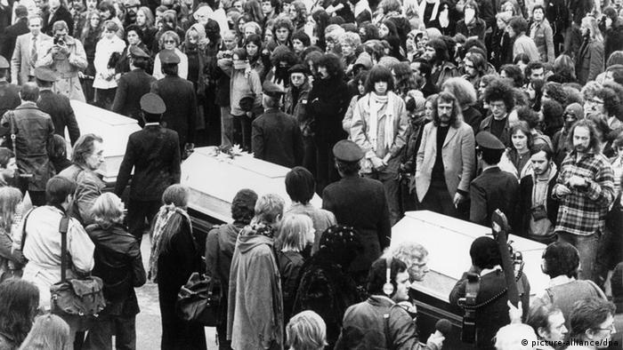 Três caixões em meio a muitas pessoas