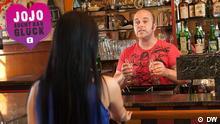 Jojo unterhält sich in einer Bar mit dem Barkeeper.