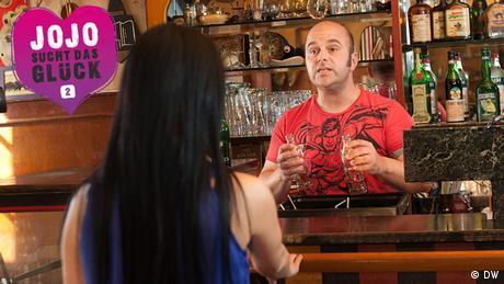 Jojo unterhält sich mit einem Barkeeper am Tresen einer Bar. (DW)