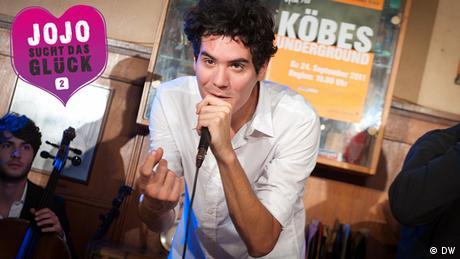 Ein junger Mann singt mit Mikrofon in der Hand.