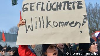 A Welcome Refugees placard at a counter-demonstration (Photo: Marc Tirl/dpa)