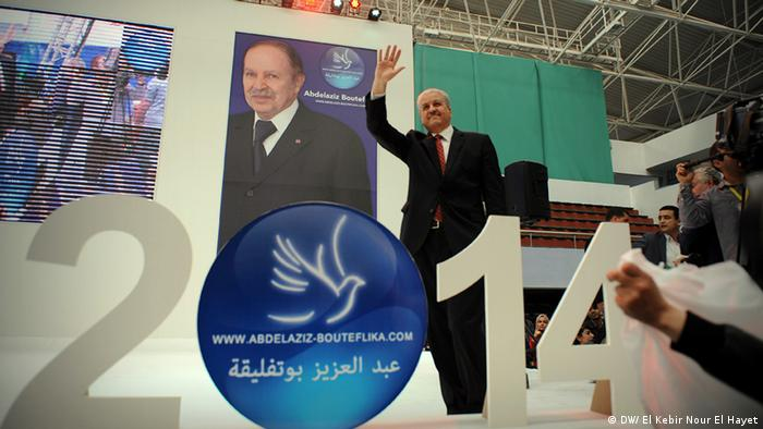 Abdelmalek Sellal in front of a poster of Bouteflika