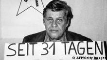 Black and white photo of Hanns-Martin Schleyer holding a sign reading 'For 31 Days' (AFP/Getty Images)