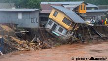 In this Friday, April 4, 2014 photo, a building teeters on the edge of a river in Honiara, Solomon Islands. Flash floods in the Solomon Islands have killed 14 people and left thousands more homeless, authorities said Saturday. (AP Photo/Solomon Star) EDITORIAL USE ONLY