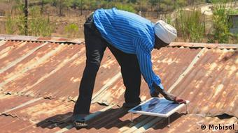 A picture of a man installing a solar panel on a roof