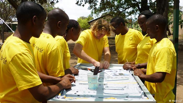 A picture of a German technician with six young Africans