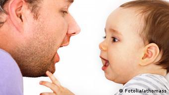 Symbolbild fürs Sprechenlernen: ein Vater (links) und ein Baby. Das Baby amt die Mundbewegung des Vaters nach.