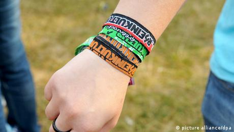 A women with lots of festival entrance wristbands on her hand