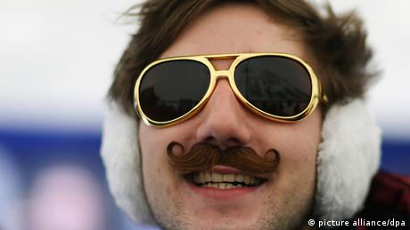 A hipster with golden glasses, a fake moustache and ear muffs