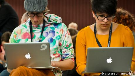 Two hipsters staring at their Apple laptops