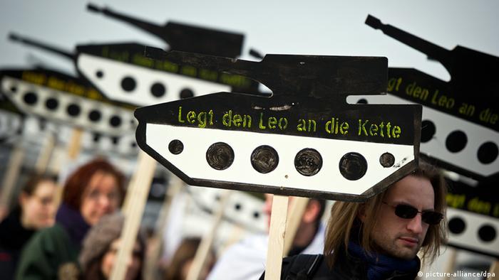 Menschen demonstrieren mit Papppanzern, auf denen Legt Leo an die Leine steht, gegen die deutsche Rüstungsindustrie (Foto: Daniel Naupold/dpa)