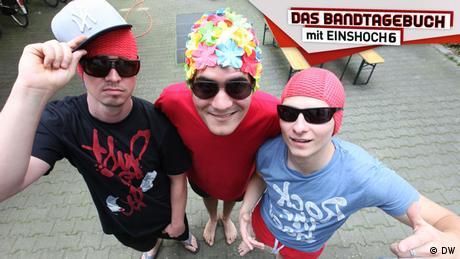Drei junge Männer mit Badekappen und Sonnenbrillen lächeln in die Kamera. (DW)