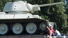Ein Junge aus Holland lässt sich am Mittwoch (15.08.2012) vor einem Panzer am sowjetischen Ehrenmal am Tiergarten bei sonnigen Wetter ablichten. Das Ehrenmal Tiergarten wurde auf Befehl der Roten Armee von deutschen Arbeitskräften unmittelbar nach Ende des Zweiten Weltkrieges als erstes sowjetisches Ehrenmal im Zentrum der Stadt - unweit von Brandenburger Tor, Reichstagsgebäude und Hitlers Reichskanzlei im Tiergarten - errichtet und bereits am 11. November 1945 eingeweiht. Foto: Maurizio Gambarini dpa/lbn +++(c) dpa - Bildfunk+++