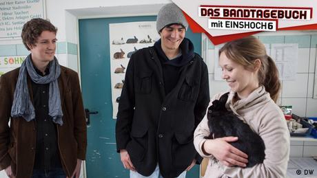 Zwei Musiker der Band EINSHOCH6 stehen neben einer Tierheim-Mitarbeiterin, die ein Kaninchen auf dem Arm hält.
