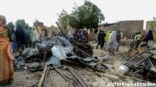 epa04107797 A photograph made available 03 March 2014 shows Nigerians look on at damage from a bomb blast at Binta Suga market that claimed 51 lives in Maiduguiri, Nigeria 02 March 2014. According to local reports the blast is believed to be the work of Islamist militant group Boko Haram. The incident took place late 01 March hours after another two bomb blasts killed more than 50 in Maiduguri. Boko Haram has been resposible for violence over the past four years in its demand for Islamic rule in northern Nigeria. EPA/DEJI YAKE +++(c) dpa - Bildfunk+++