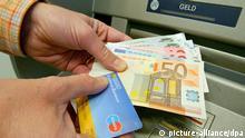 EU-Parlament stimmt ab ARCHIV - ILLUSTRATION - Ein Kunde zieht am 02.11.2006 am Geldautomaten einer Bank in Frankfurt am Main Geldscheine. Das Recht auf ein Girokonto, die Bankenabwicklung und die Einlagensicherung: Zahlreiche gewichtige Themen stehen auf der Tagesordnung des EU-Parlaments. Foto: Salome Kegler/dpa (zu dpa «EU-Parlament stimmt über Banken, Konten und Alternativkraftstoffe ab» vom 15.04.2014) +++(c) dpa - Bildfunk+++