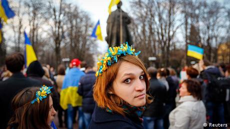 Жінка із жовто-блакитною символікою на тлі натовпу із синьо-жовтини прапорами на акції на підтримку України в Луганську, 15 квітня 2014 року
